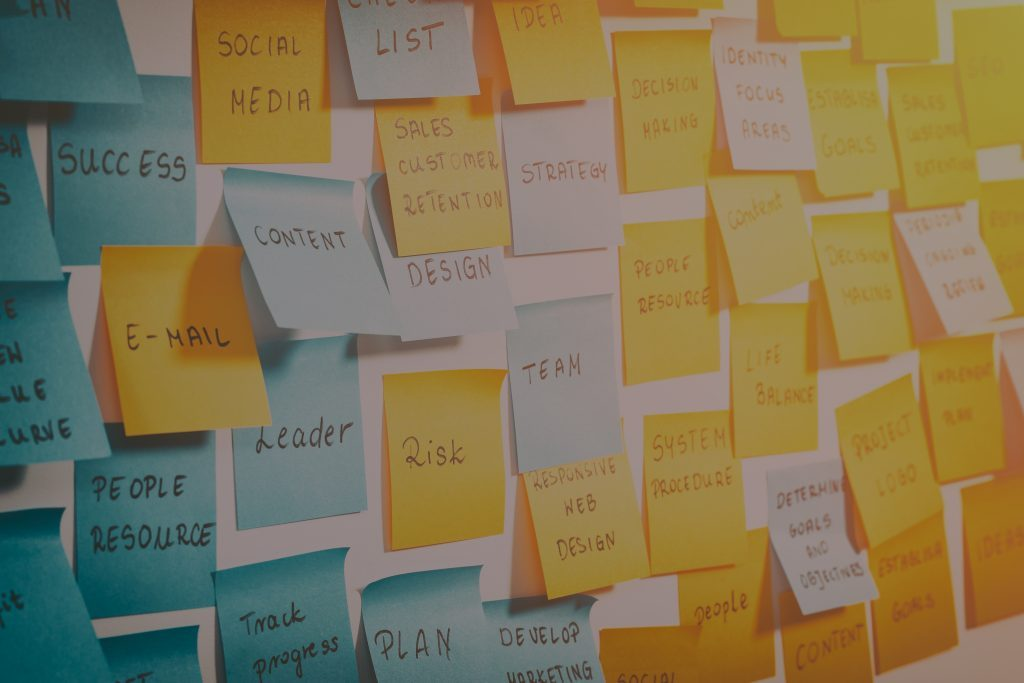White wall with yellow and blue sticky notes on with important words on